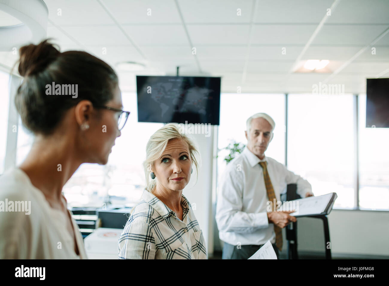Mature businesswoman listening t her colleague with man standing in background. Business people having a informal - Stock Image