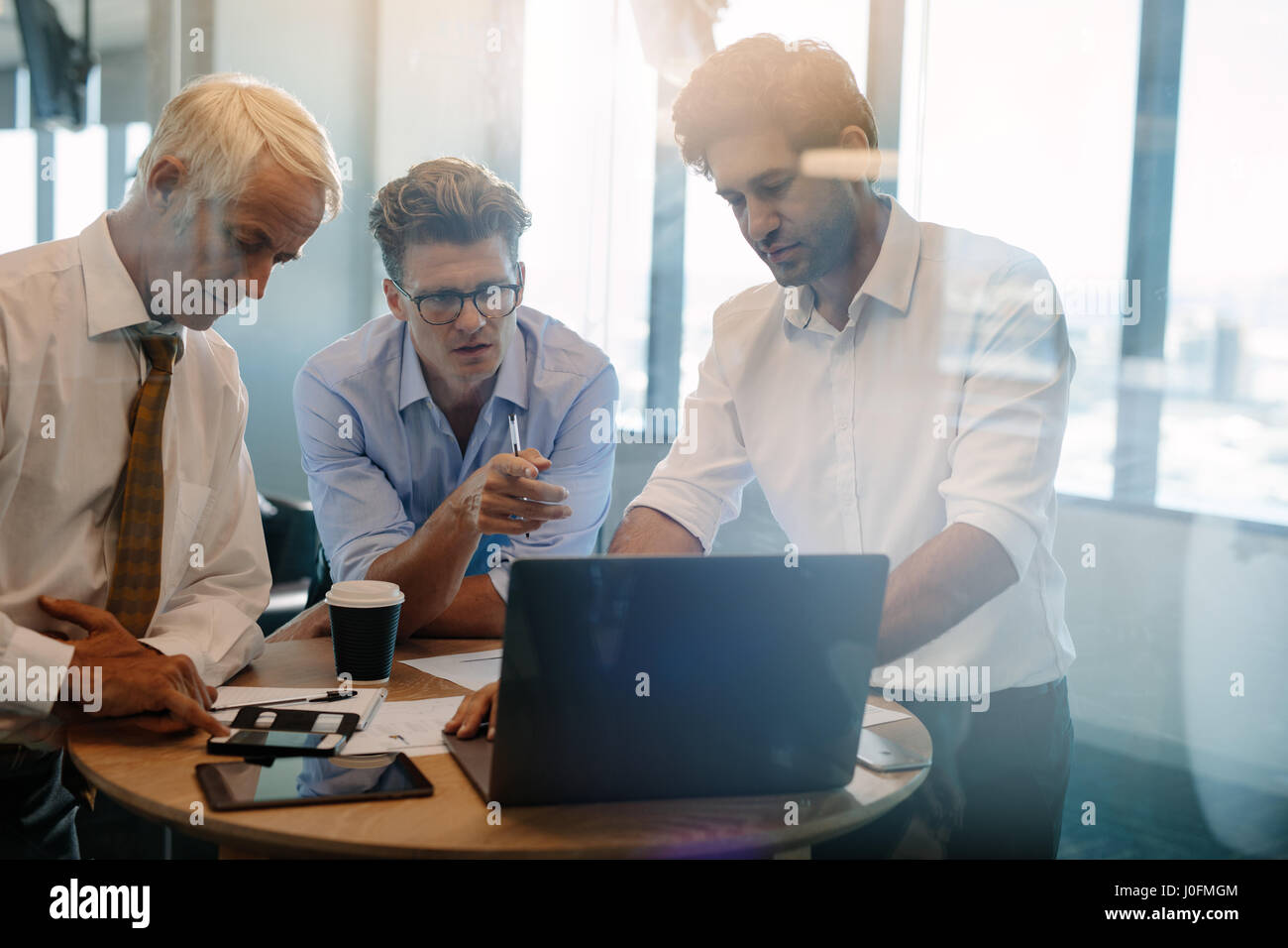 Business people talking while standing by table in office. Businessman giving demonstrating on laptop to colleagues Stock Photo