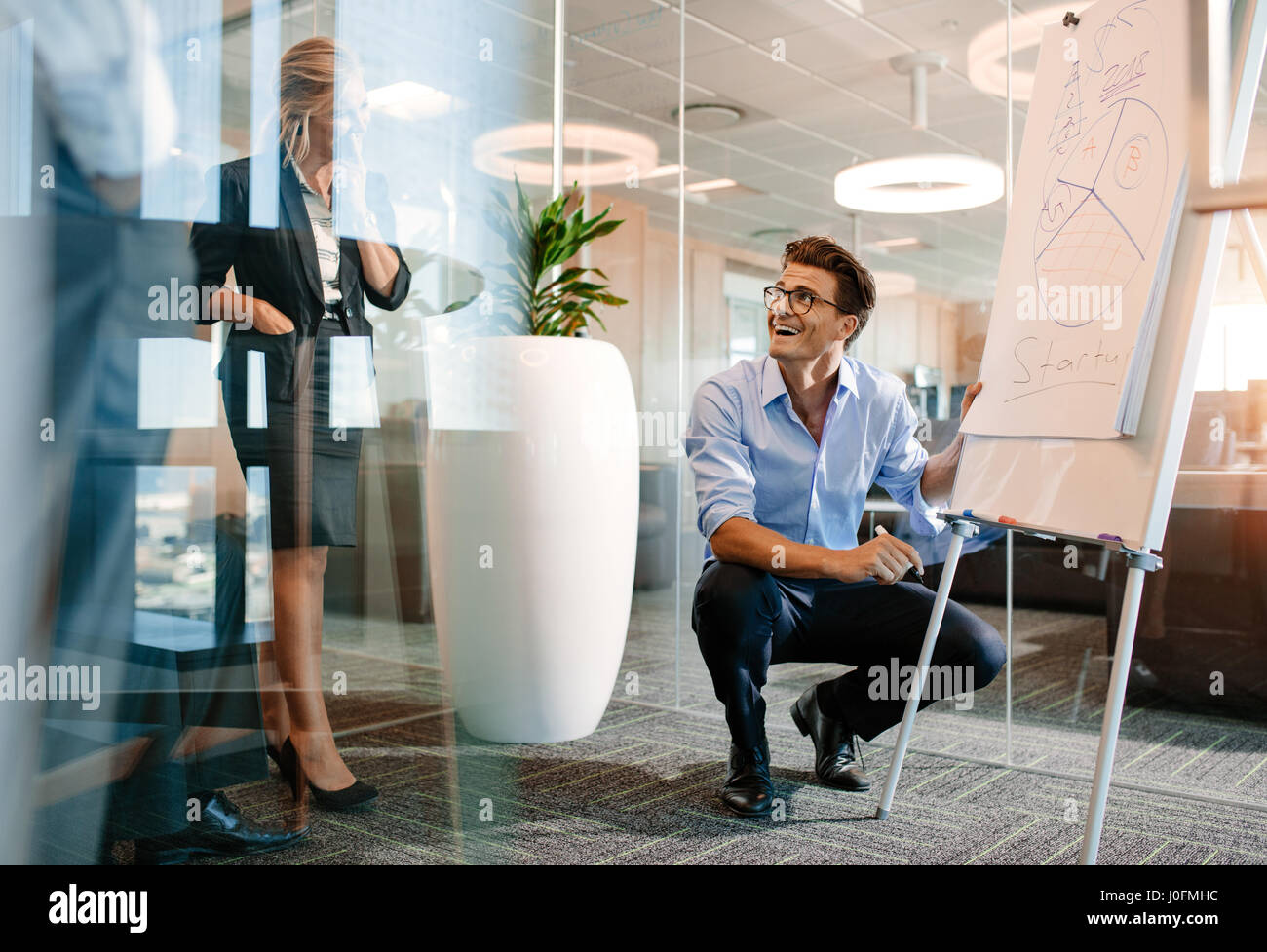 Happy mature caucasian businessman near flip board with diagram. Office worker giving a presentation on a flipchart - Stock Image