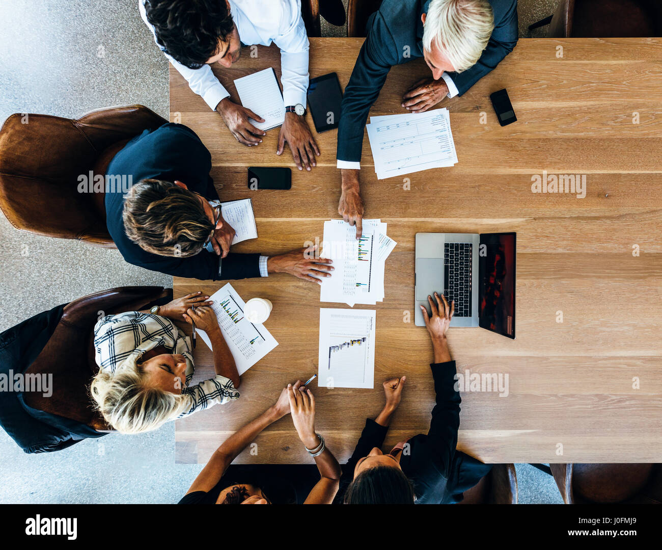 Team of business people sitting together in discussion. Top view shot of business colleagues discussing financial - Stock Image