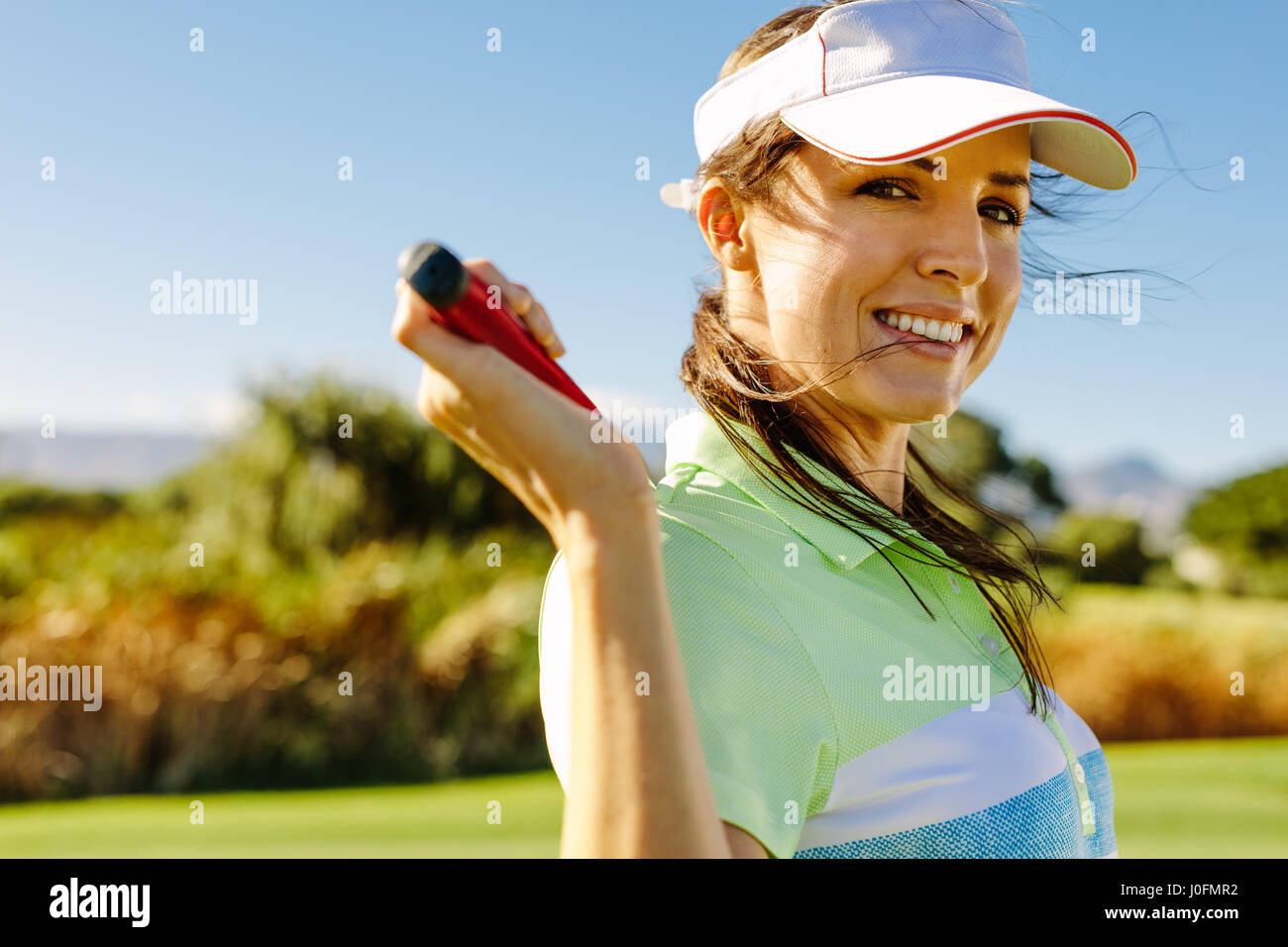 Close up portrait of happy female golfer holding golf club on field. Beautiful young woman standing on golf course - Stock Image