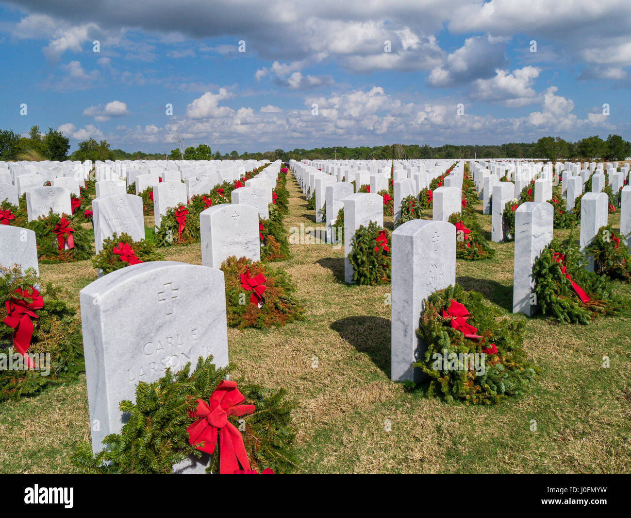 Rows of grave stones with wreaths & red bows in Sarasota National Cemetery in Sarasota Florida - Stock Image