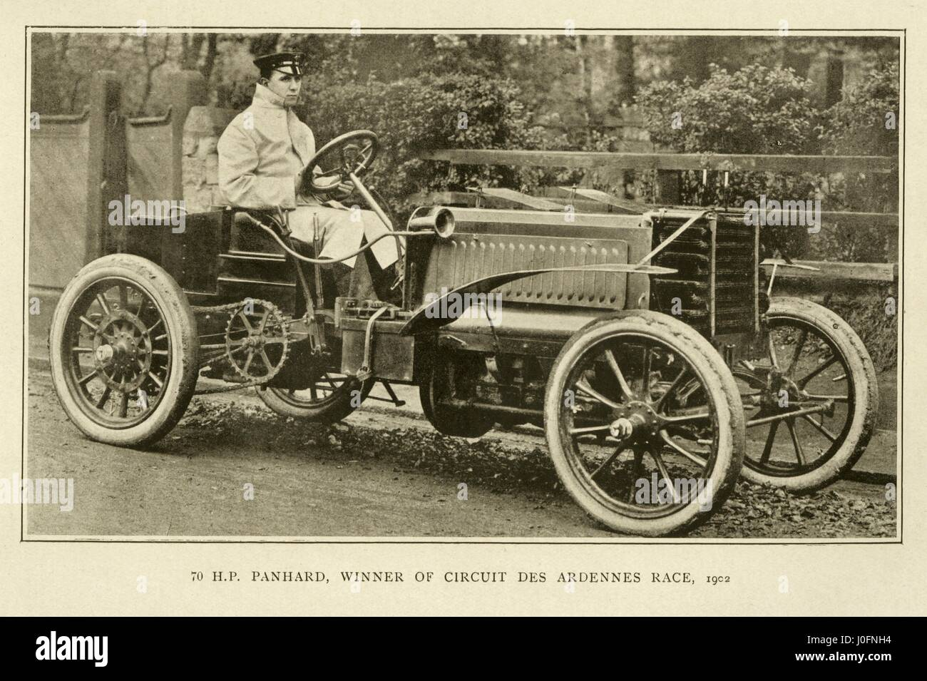 A man seated on a 70 Horse Power Panhard racing car, winner of the ...