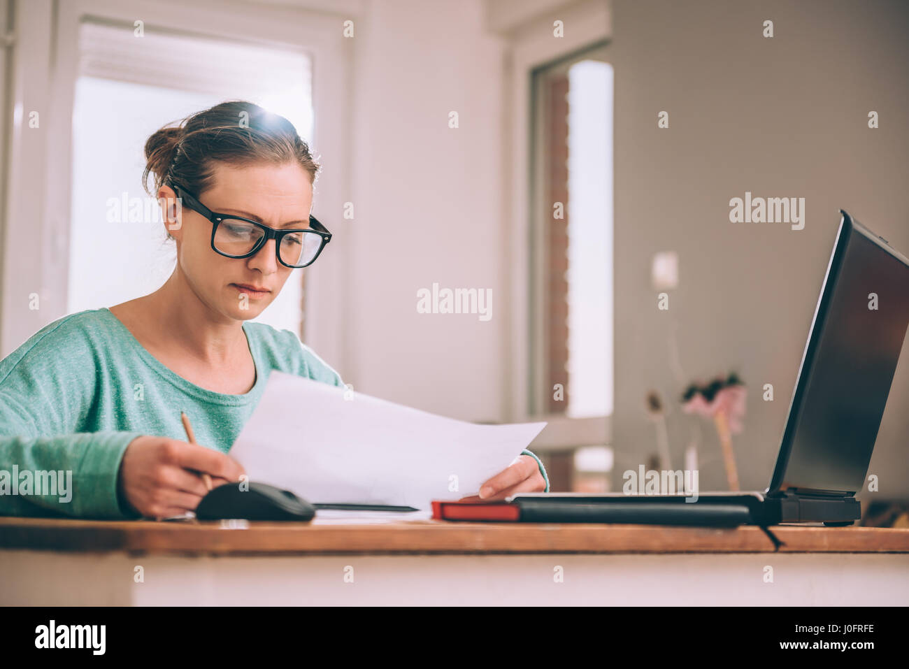 Woman wearing eyeglasses sitting at a desk at home and doing paperwork - Stock Image