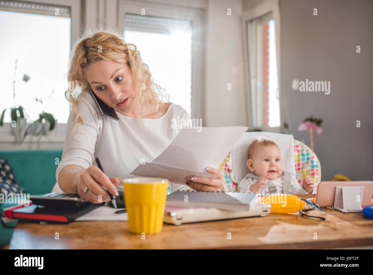 Mother holding letter, writing notes, talking on smart phone at home office and taking care of her baby - Stock Image