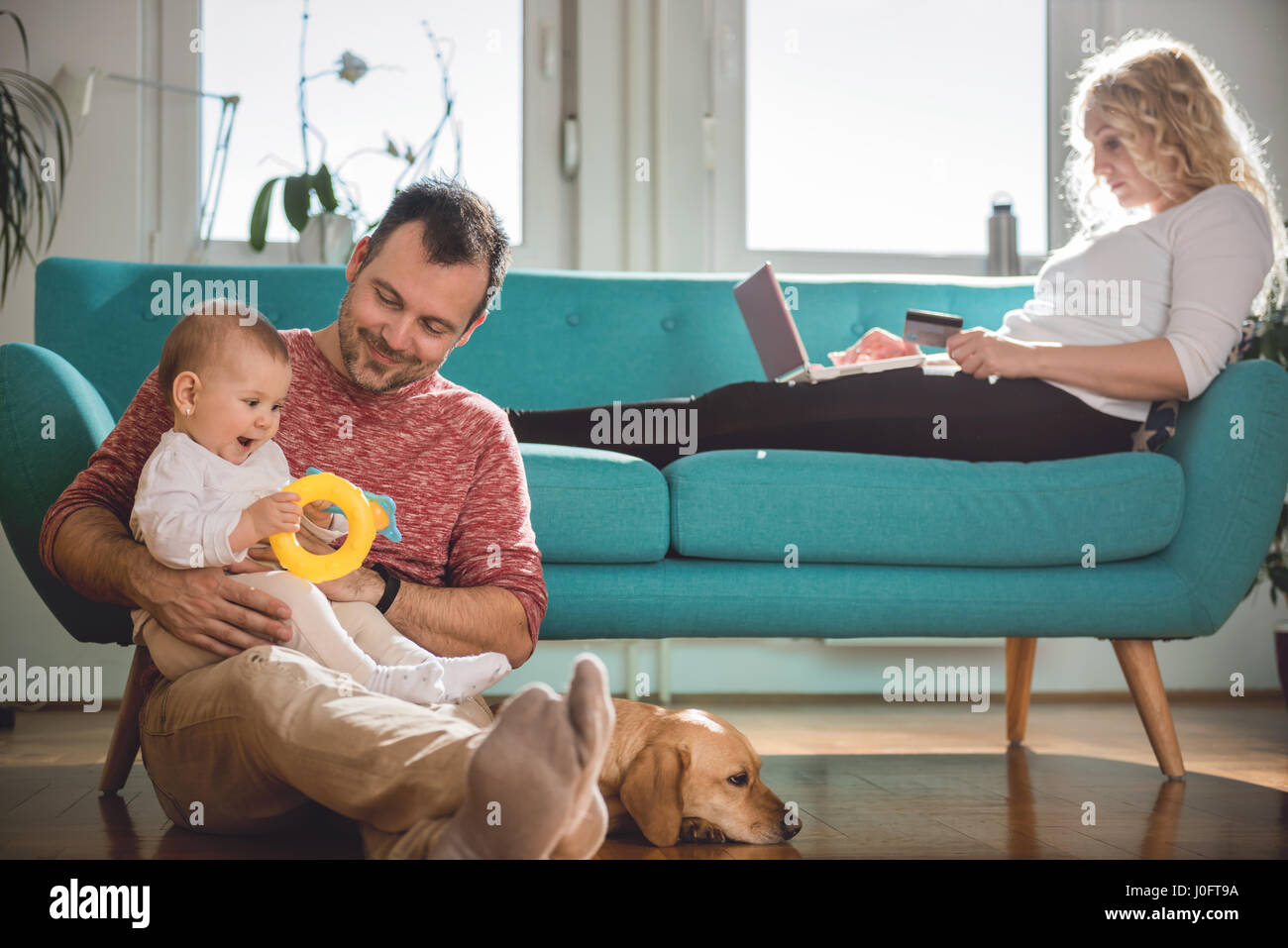 Father sitting on the floor and holding baby in his arms while wife sitting on sofa and doing online shopping with Stock Photo
