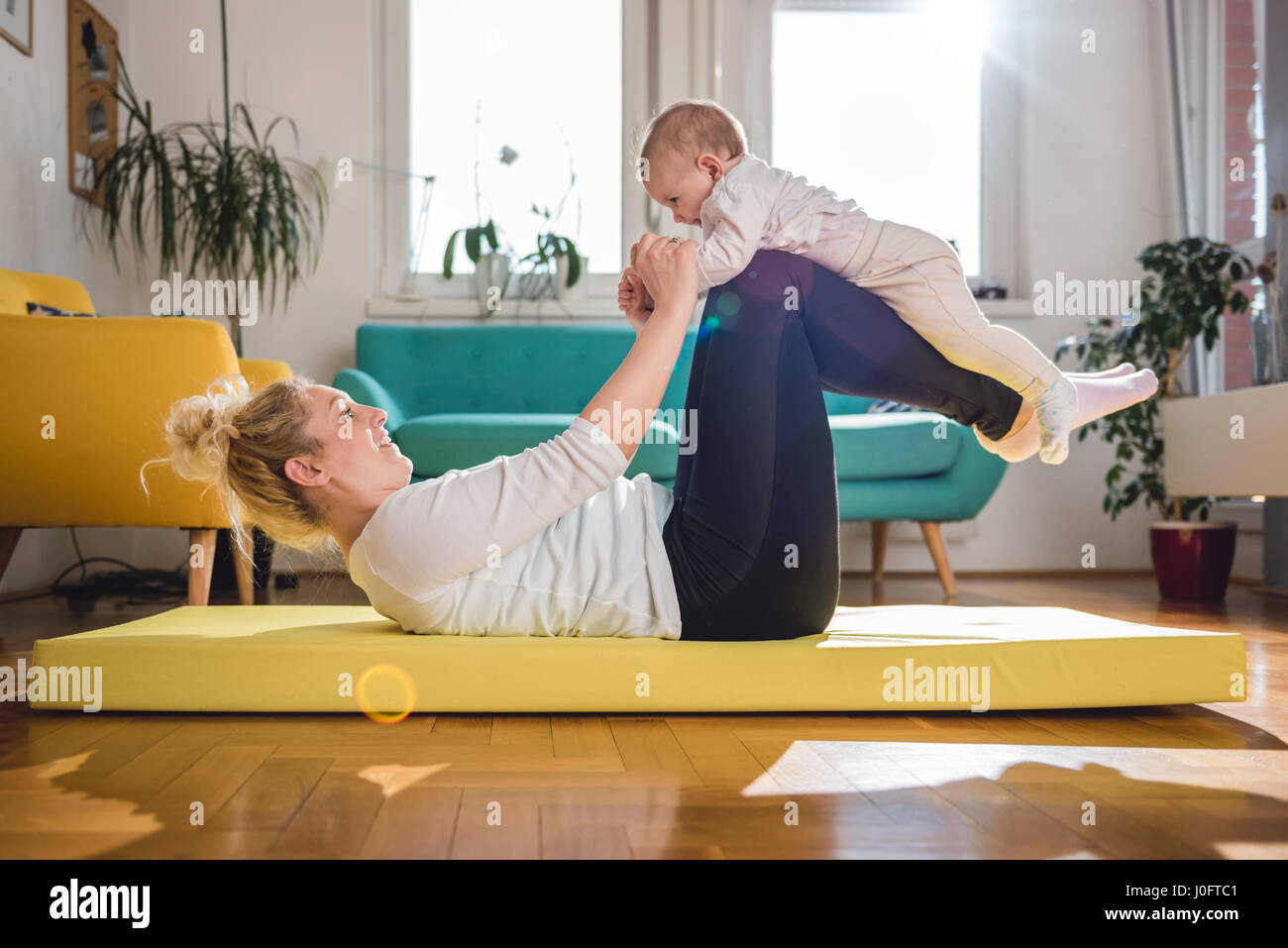 Mother Exercise With Her Baby on yellow mat At Home - Stock Image