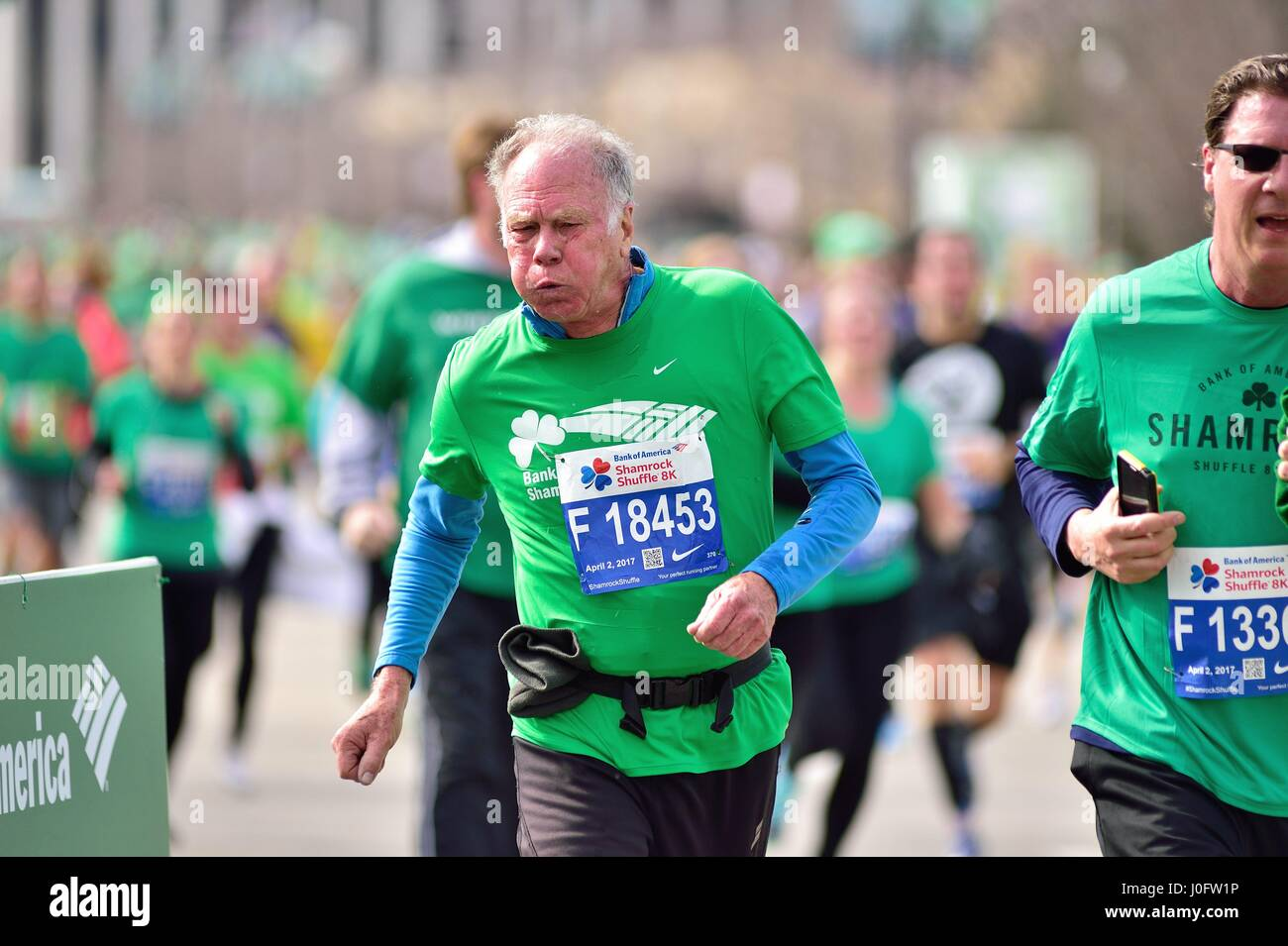 Fatigued runner straining prior to crossing the finish line at the 2017 Shamrock Shuffle race in Chicago, Illinois, - Stock Image