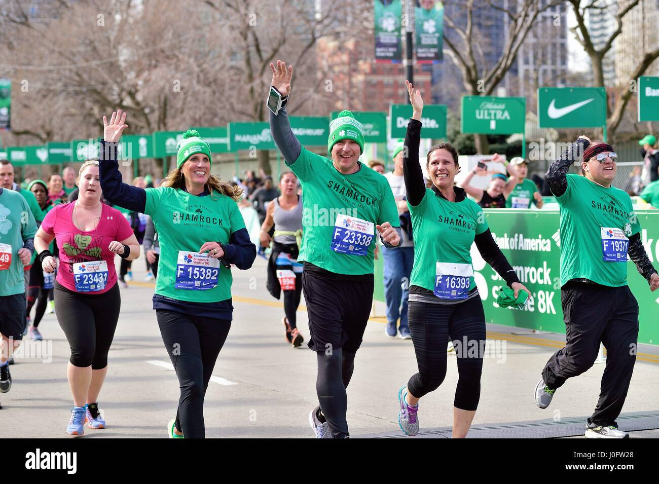 Happy cluster of runners crossing the finish line at the 2017 Shamrock Shuffle race in Chicago, Illinois, USA. - Stock Image