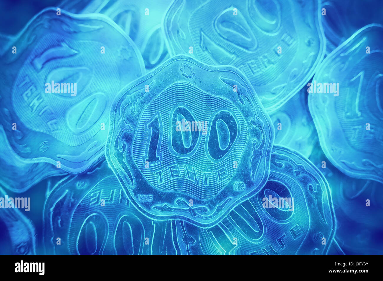Many hundreds of tenge of coins, Kazakhstan money. Cold and distorted coins as if in water, close-ups - Stock Image