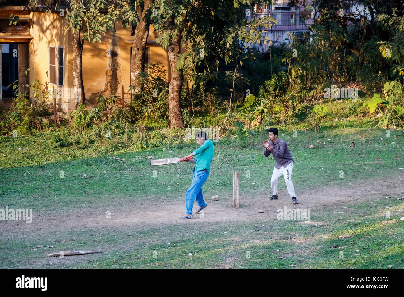 Two local Indian boys having fun playing a game of cricket on a dusty pitch in Pragpur, a heritage village in Kagra Stock Photo