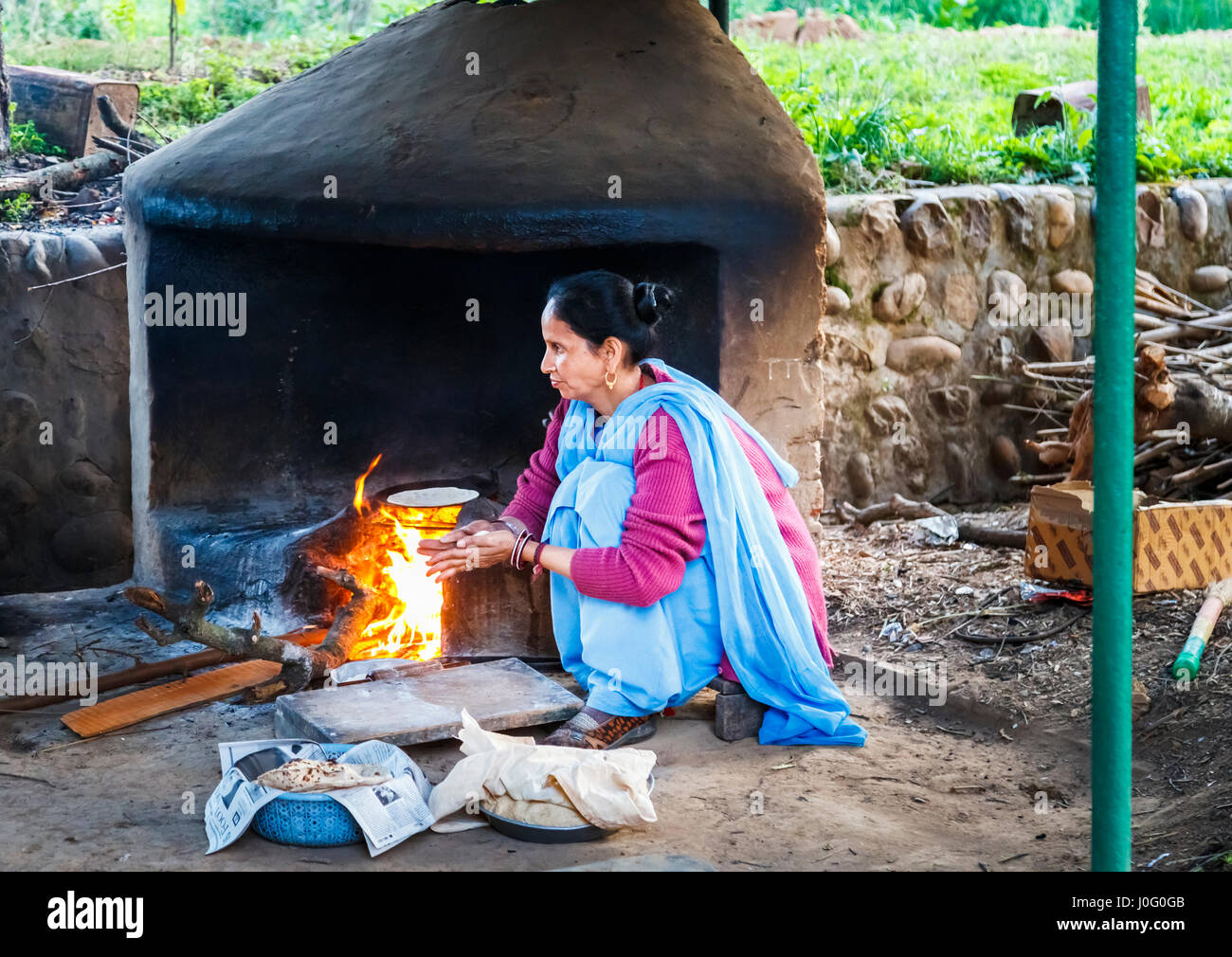 Local Indian woman wearing blue sari cooking chapatis in an oven with open fire, Judge's Court Hotel, Pragpur, - Stock Image