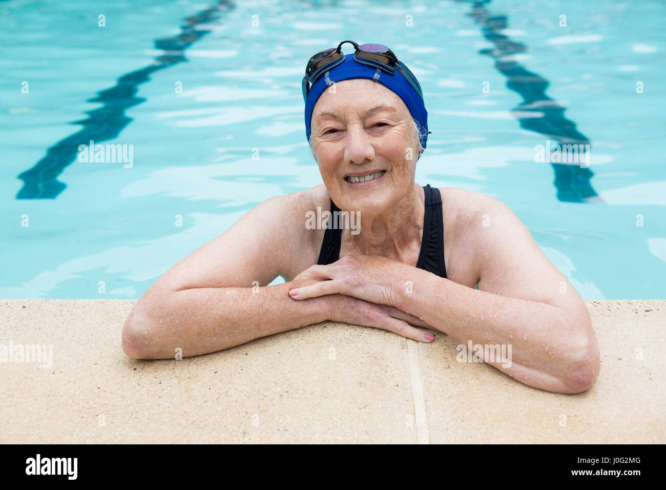 2b60f778aa7 Portrait of smiling senior woman standing in swimming pool - Stock Image