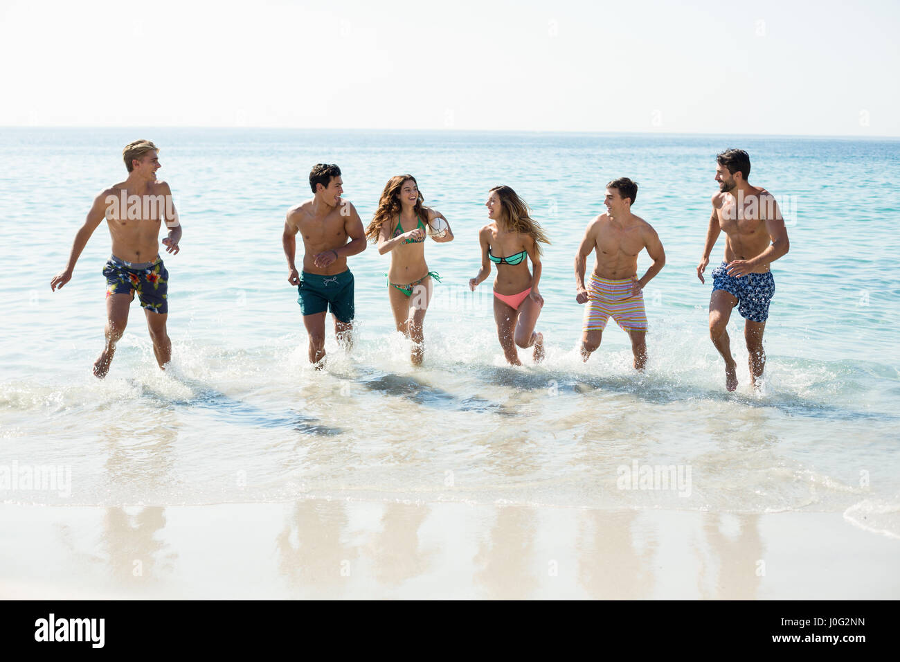 Friends running on shore at beach - Stock Image