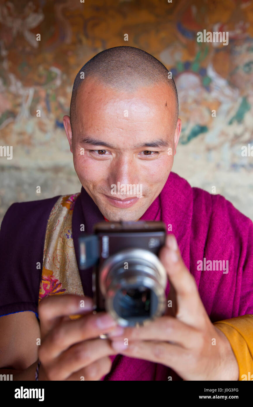 Monk with camera, Bhutan - Stock Image