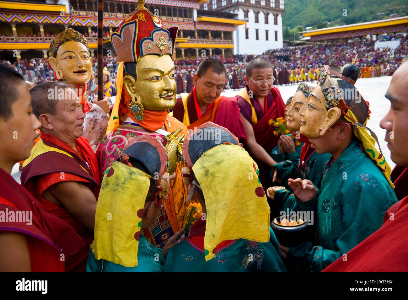 Masked figure being carried past crowd, Festival, Trashichhoe Dzong,  monastery, Thimpu, Bhutan - Stock Image
