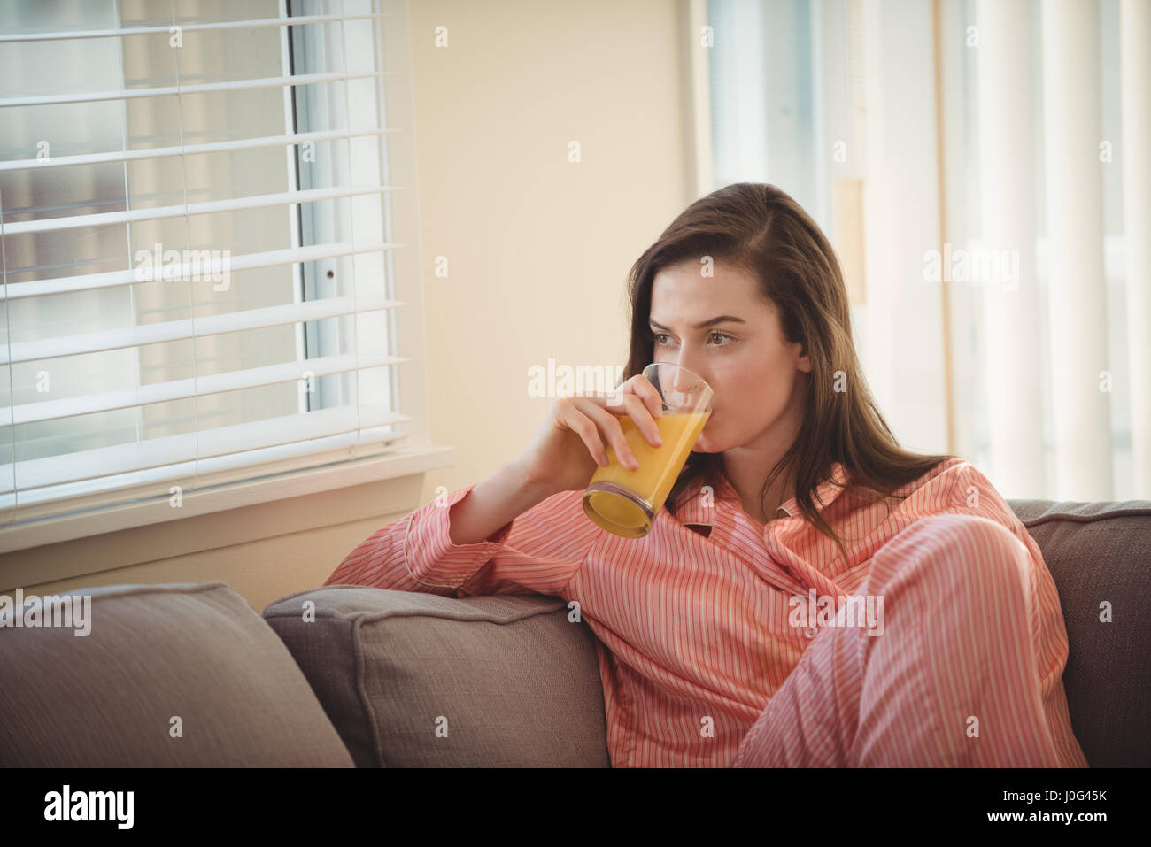Woman drinking juice while looking through window at home - Stock Image