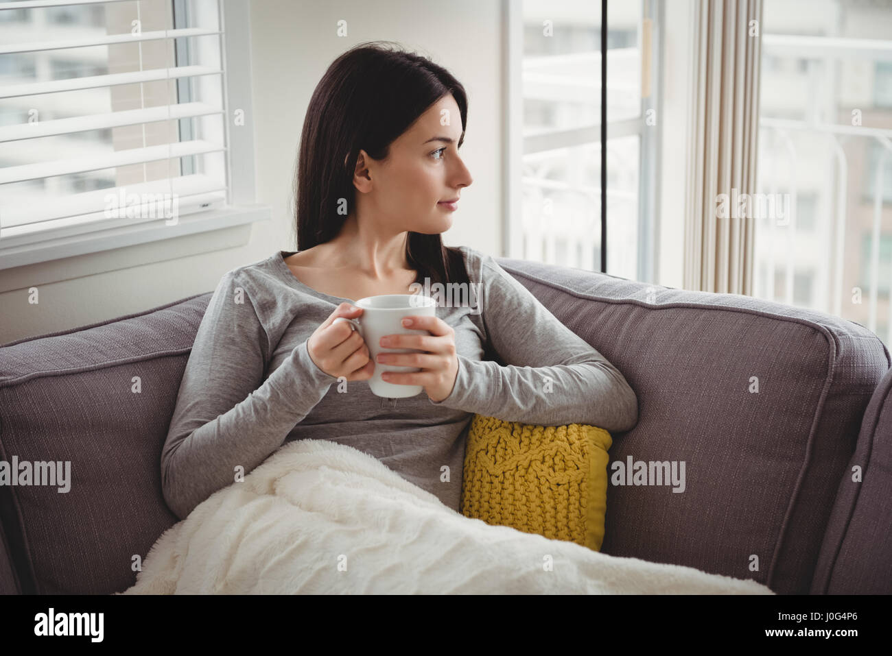 Woman holding cup while looking through window at home - Stock Image