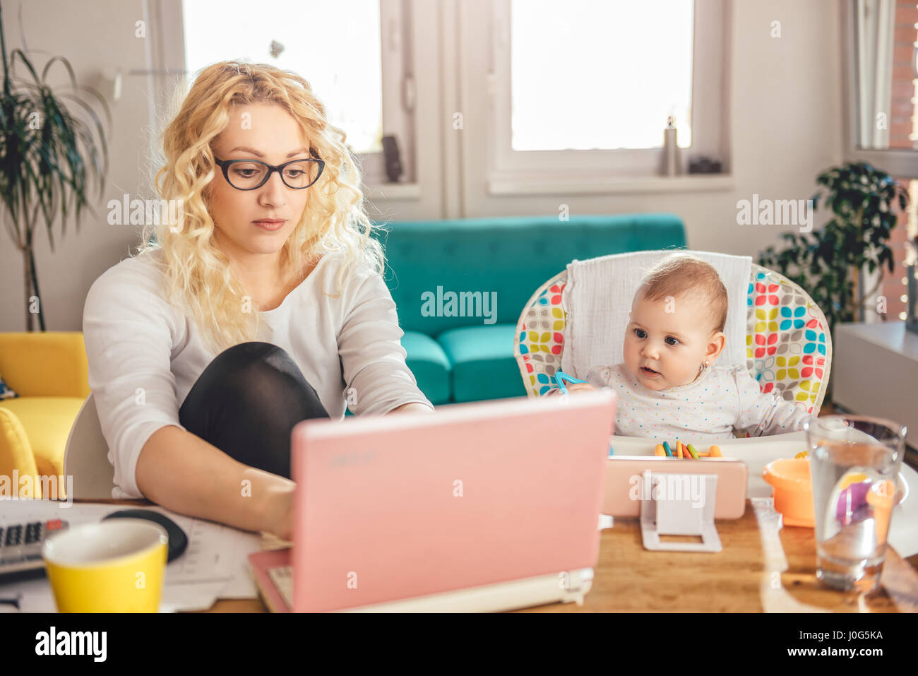 Mother wearing eyeglasses working at home office on laptop and taking care of her baby - Stock Image