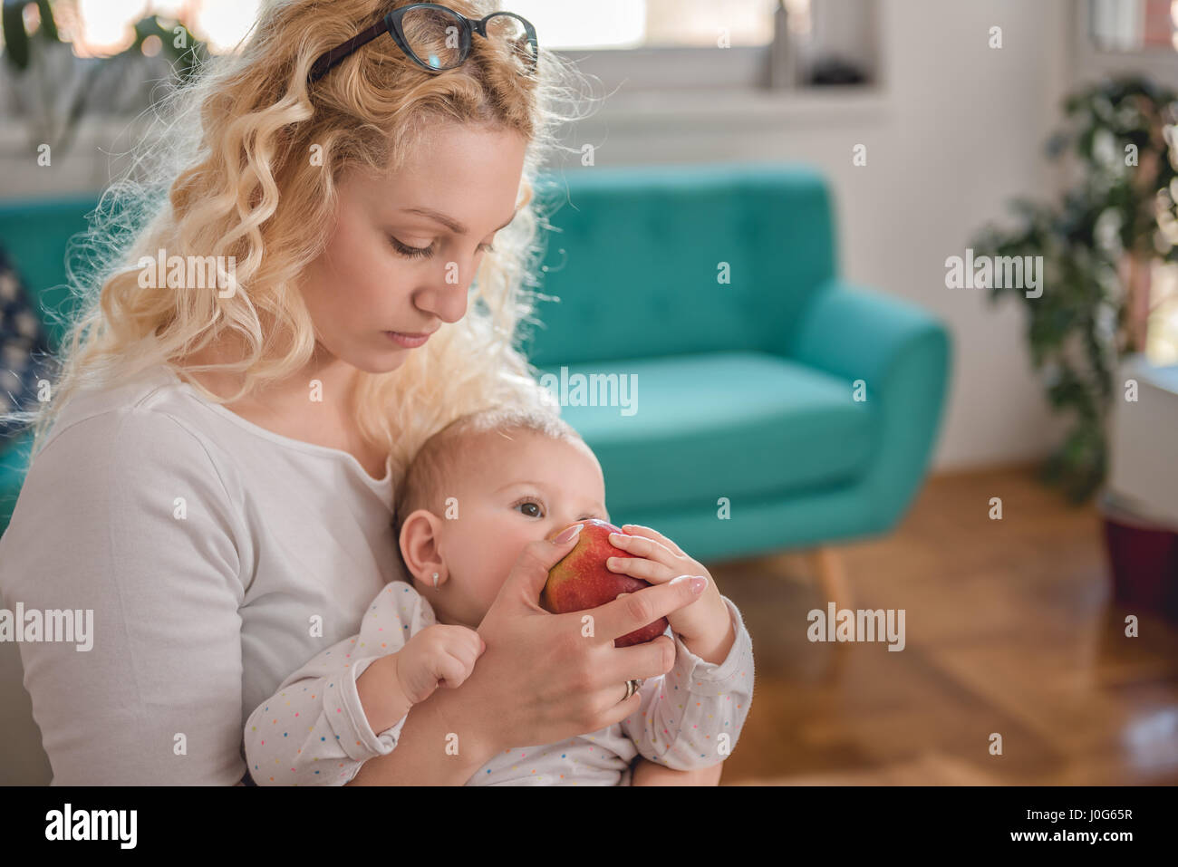 Mother feeding baby at home office with fresh red apple - Stock Image