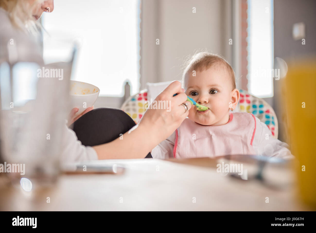Mother feeding baby at home - Stock Image