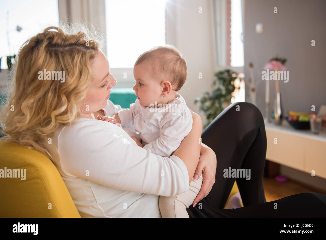 Mother holding baby in her arms and sitting at yellow armchair - Stock Image