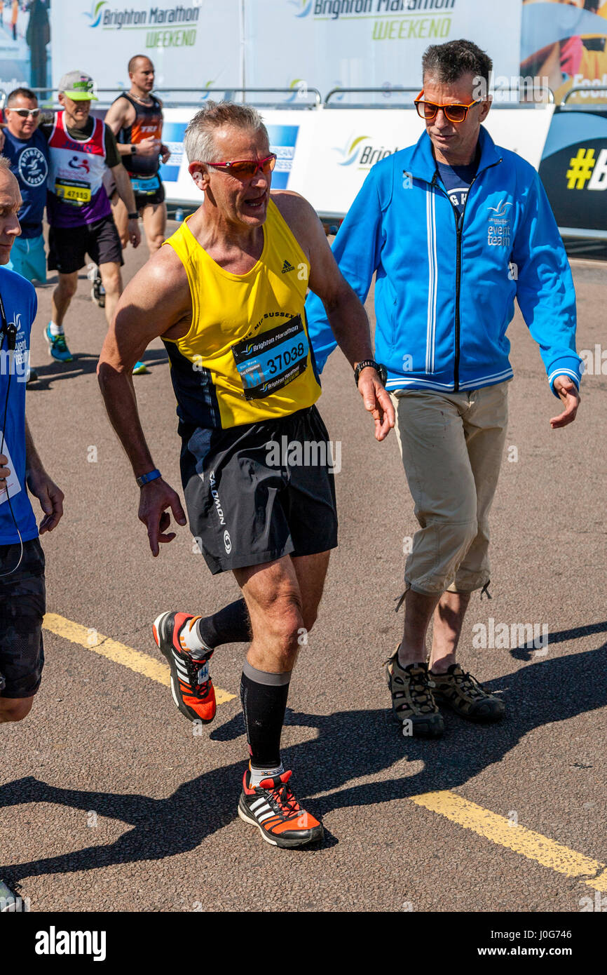 An Exhausted Elderly Athlete Approaches The Finish Line At The Brighton Marathon, Brighton, Sussex, UK - Stock Image