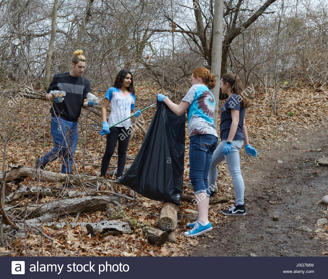High school students involved in volunteer community service school cleanup - Stock Image
