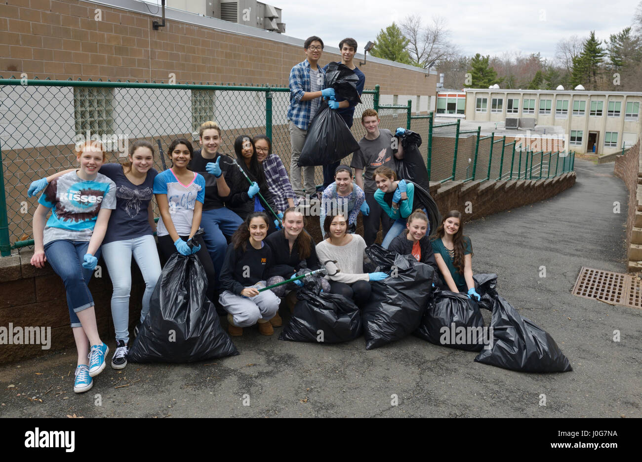 High school students after a volunteer community service school cleanup project with bags of litter - Stock Image