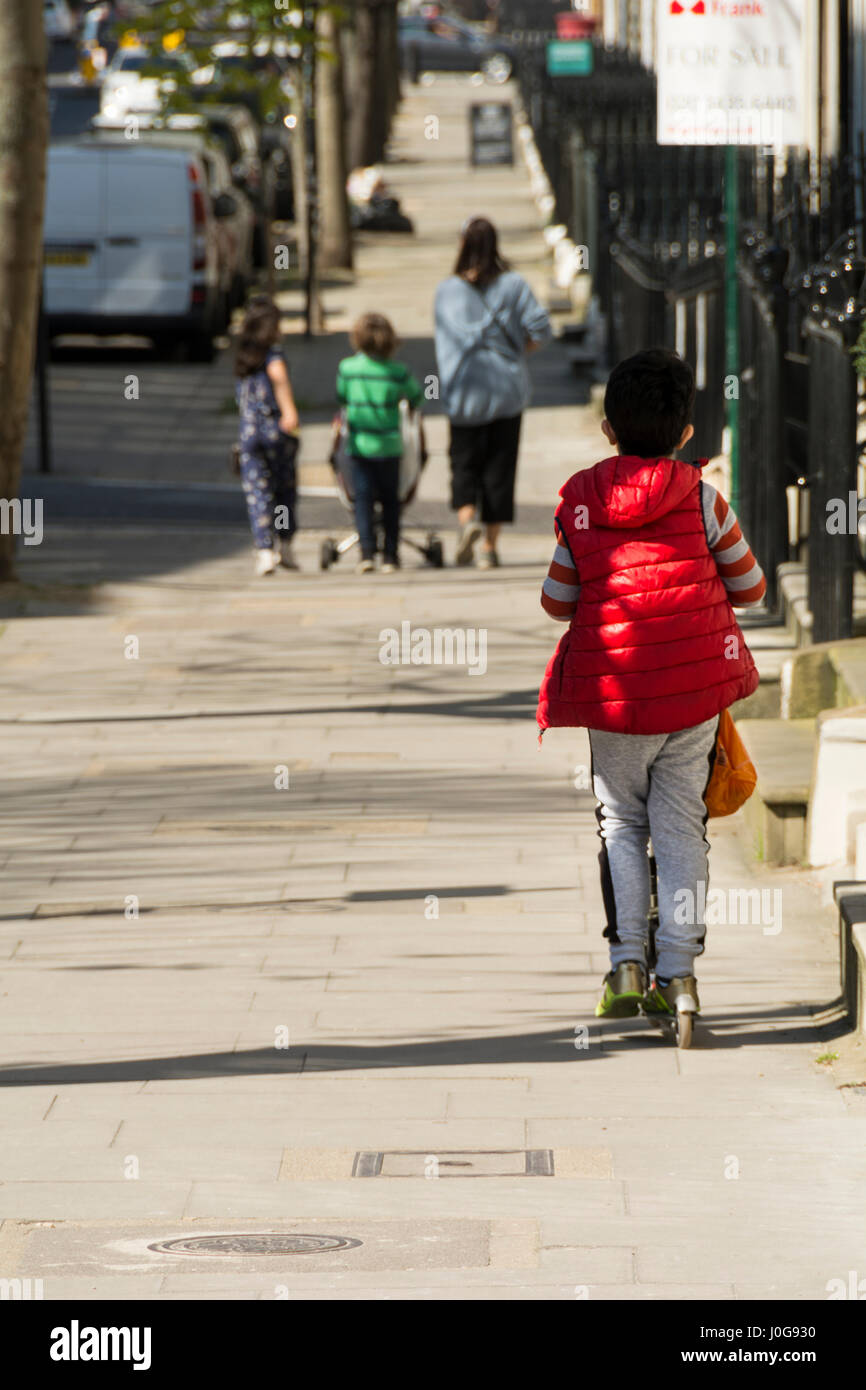 A young boy riding a scooter chases after his mother and brother and sisters on a London street - Stock Image
