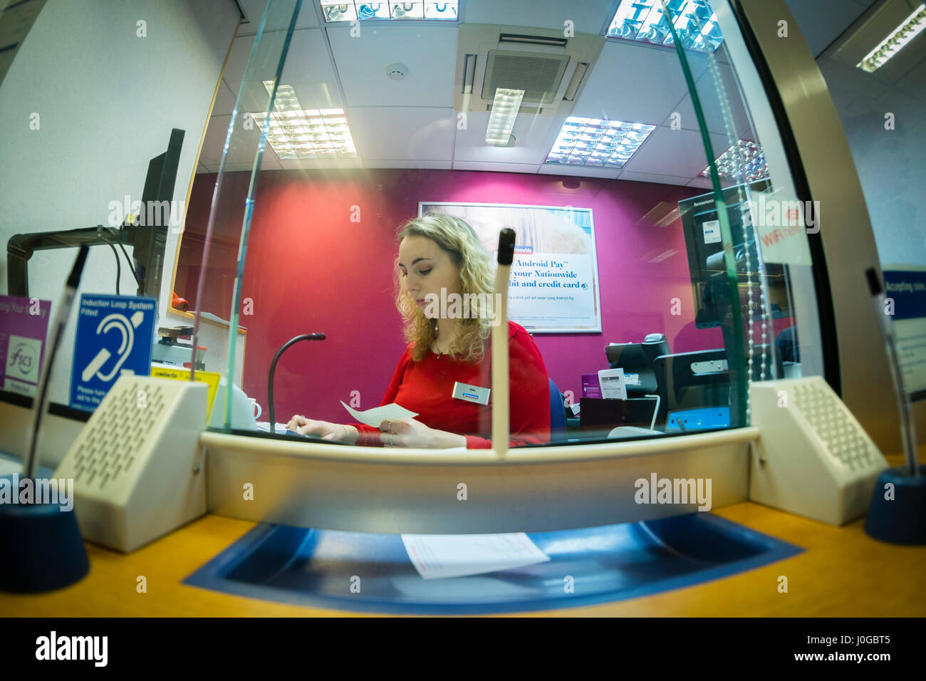 Financial Services A Young Woman Bank Teller Working Behind The