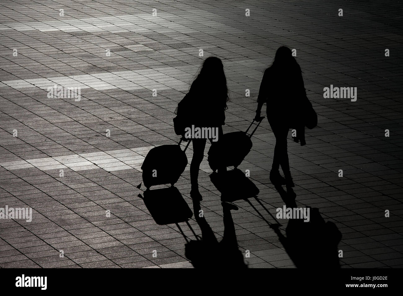Silhouete of two girls who just arrived to the airport - Stock Image