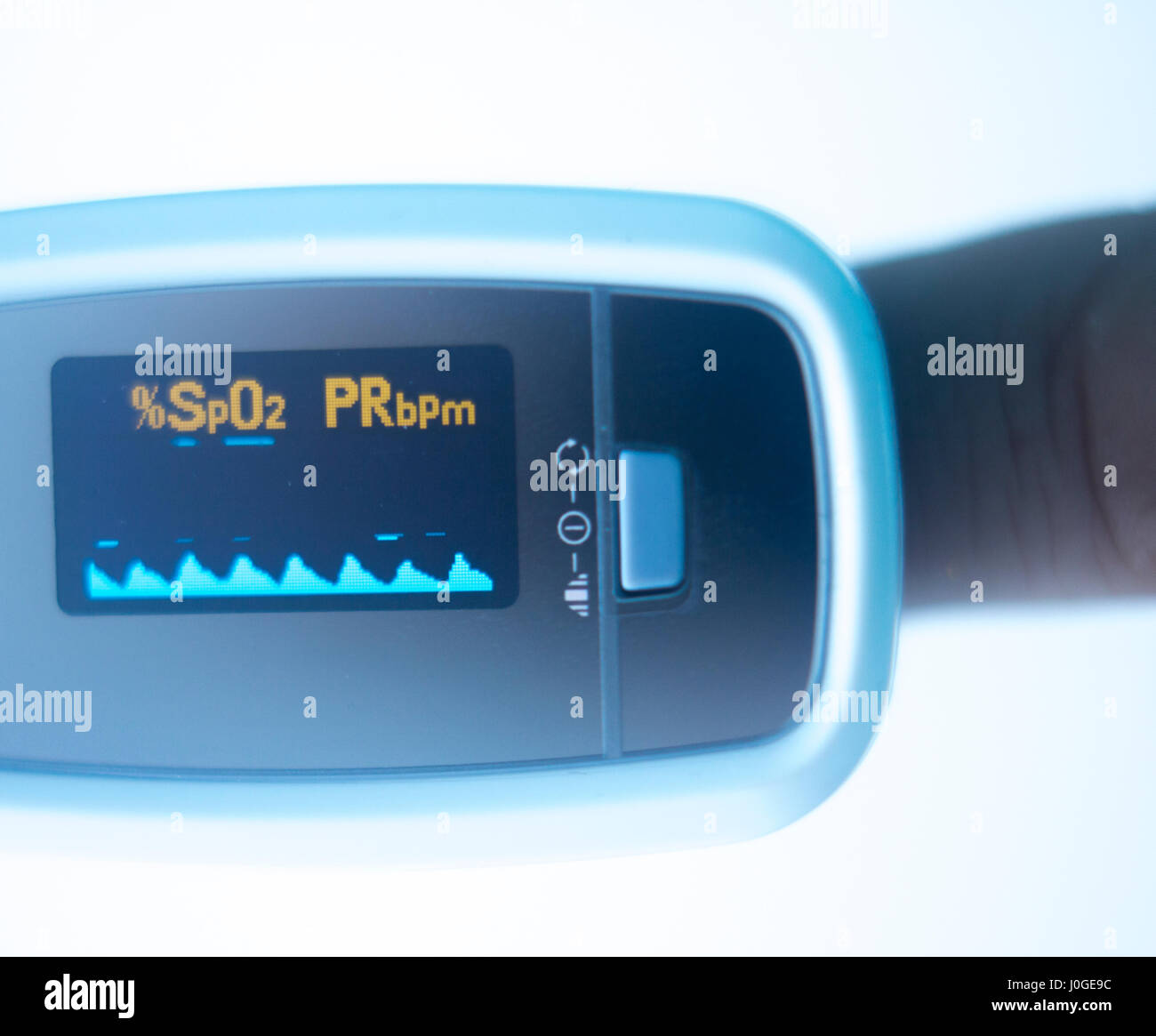 Blood pressure finger resting pulse monitor used to take heart rate and irregular beats with cardiogram. - Stock Image
