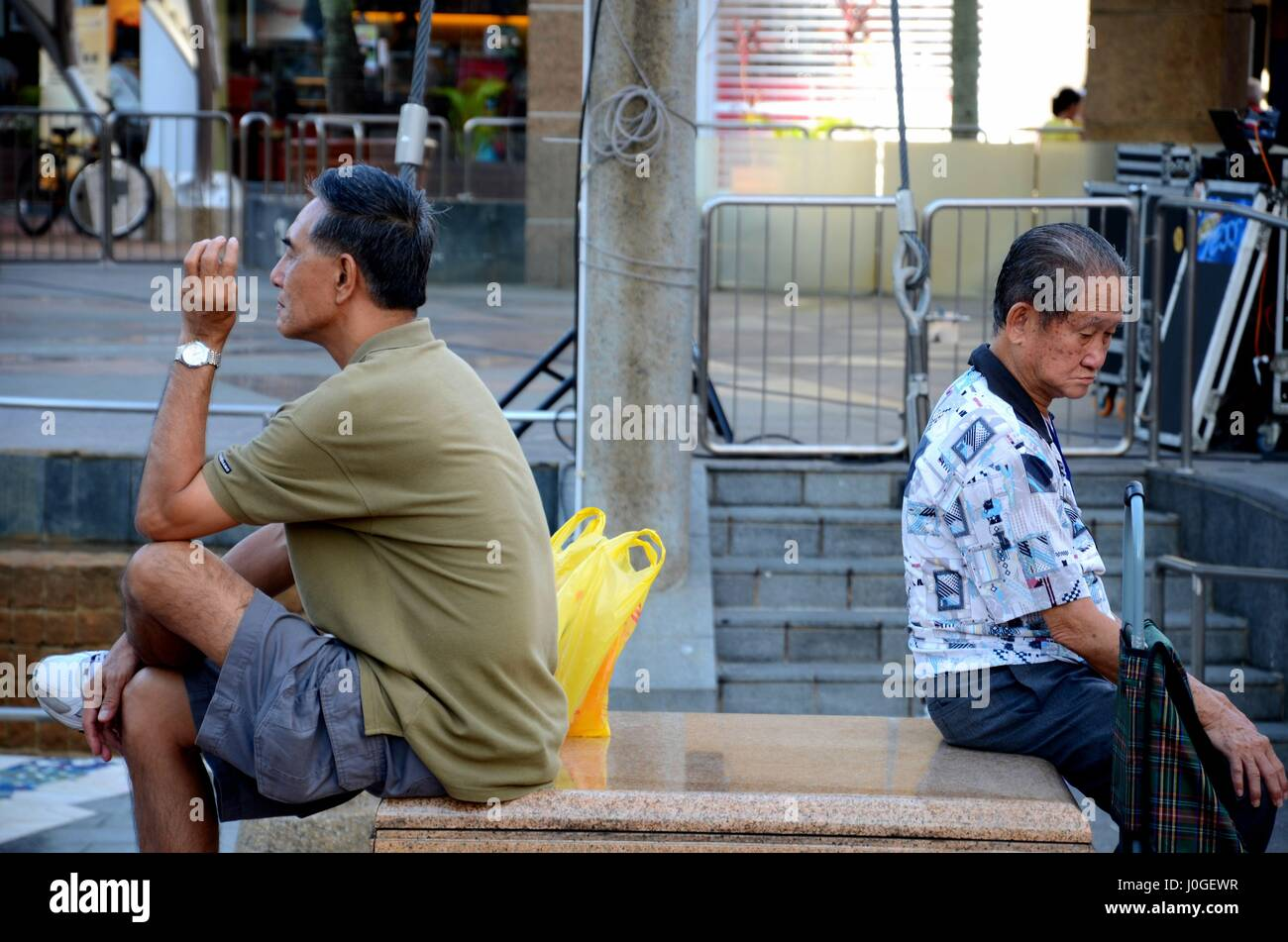 Two men sit back to back while one smokes a cigarette in a public square in Singapore Toa Payoh HDB estate - Stock Image
