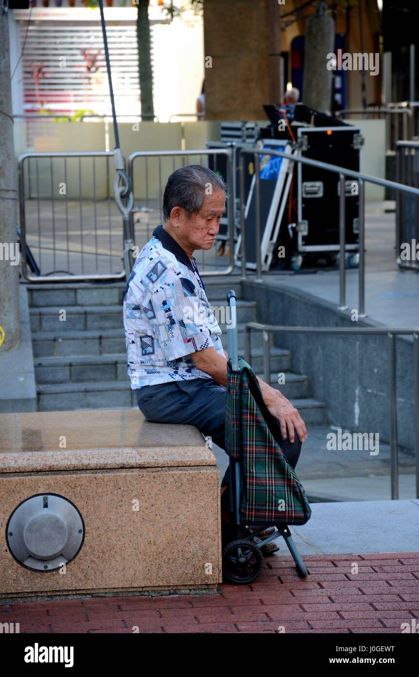 Elderly Chinese senior retiree man sits and contemplates life in Singapore Toa Payoh neighborhood - Stock Image