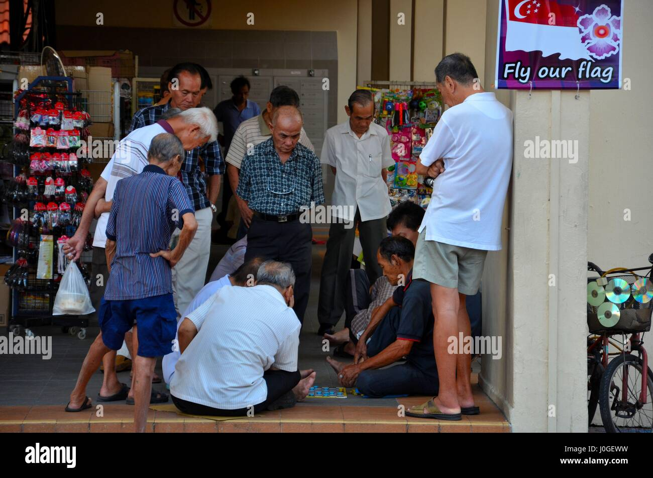Group of Chinese men watch a game of checkers and entertain themselves in Singapore Toa Payoh neighborhood - Stock Image
