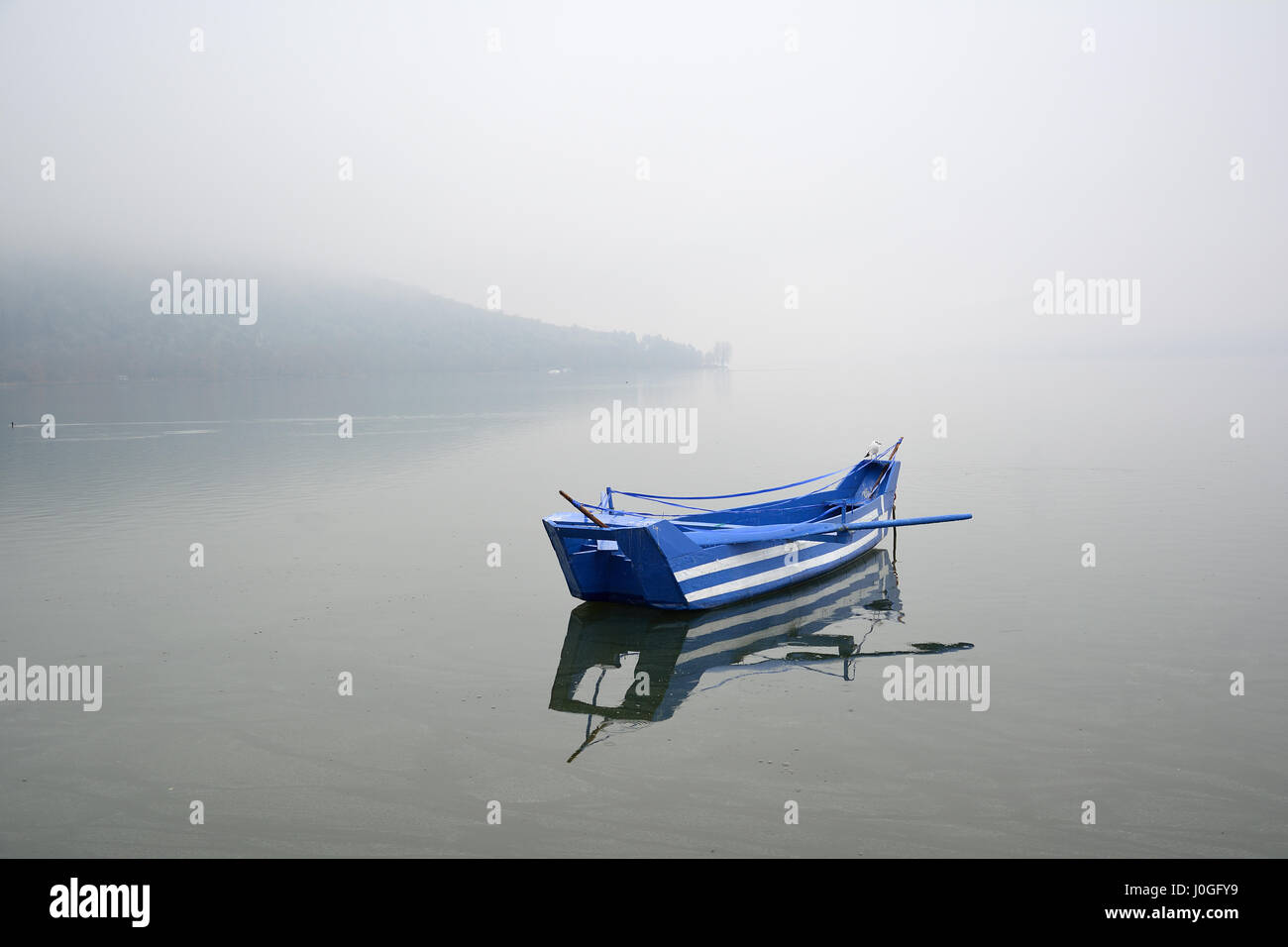 A kastorian traditional fishing boat, with greek flag painted on it, floating in calm waters on foggy day. At the - Stock Image