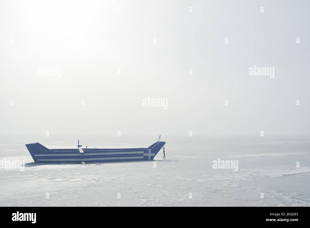 A kastorian traditional fishing boat, with greek flag painted on it, trapped in frozen lake in a misty morning - Stock Image