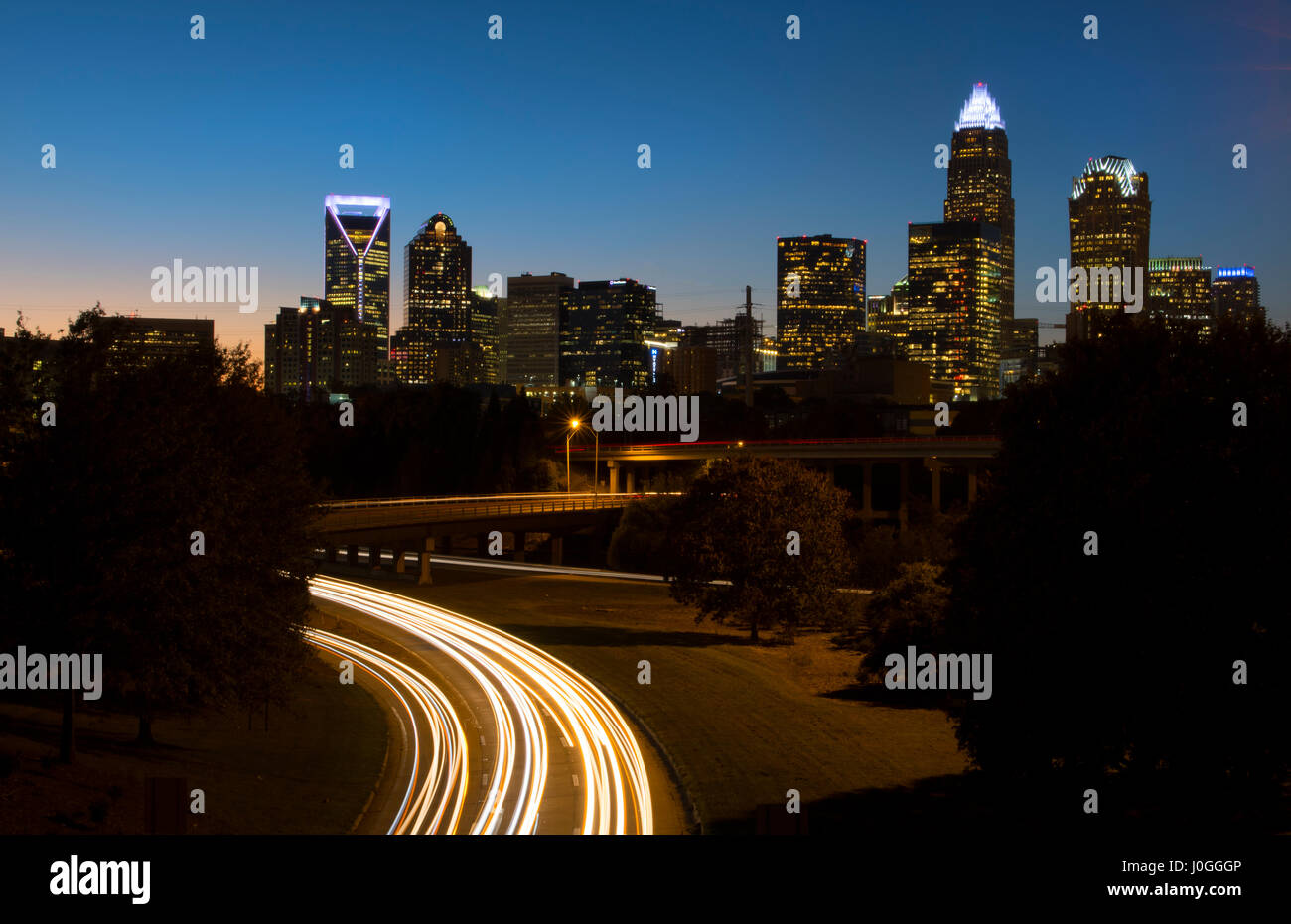 Charlotte North Carolina skyline at night with traffic blurs and twilight Stock Photo