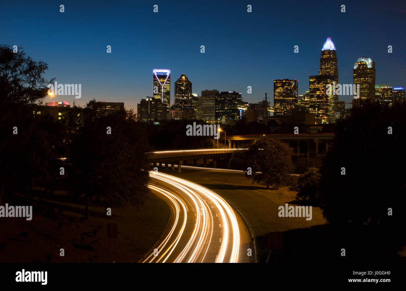 Charlotte North Carolina skyline at night with traffic blurs and twilight - Stock Image