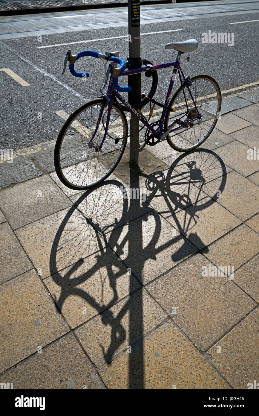 Bicycle secured to a post casts a shadow onto the pavement. - Stock Image