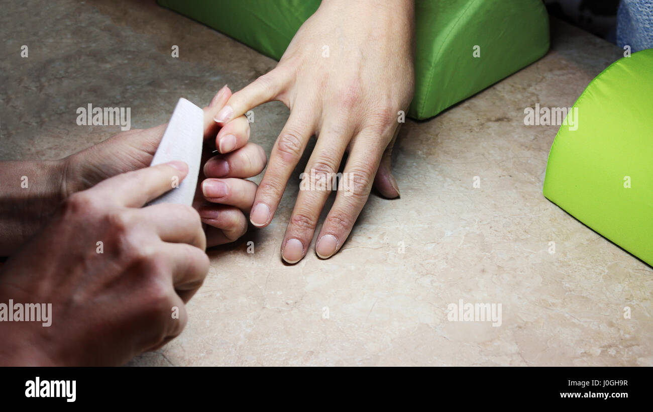 The manicurist prepares fingers of woman for applying varnish. - Stock Image