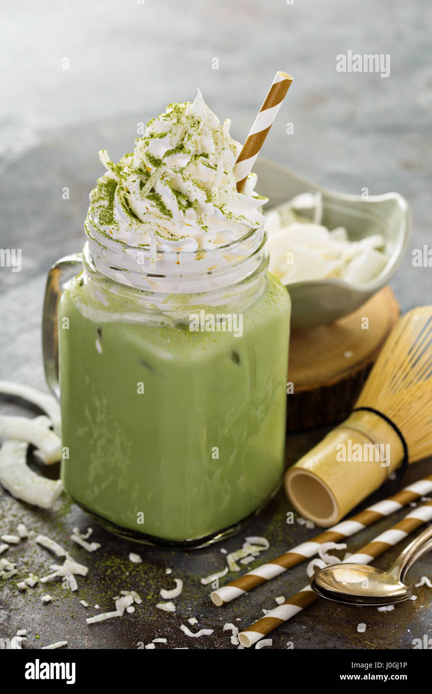 Iced matcha latte with coconut cream - Stock Image