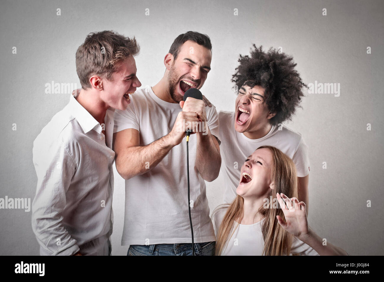 3 men and woman singing - Stock Image