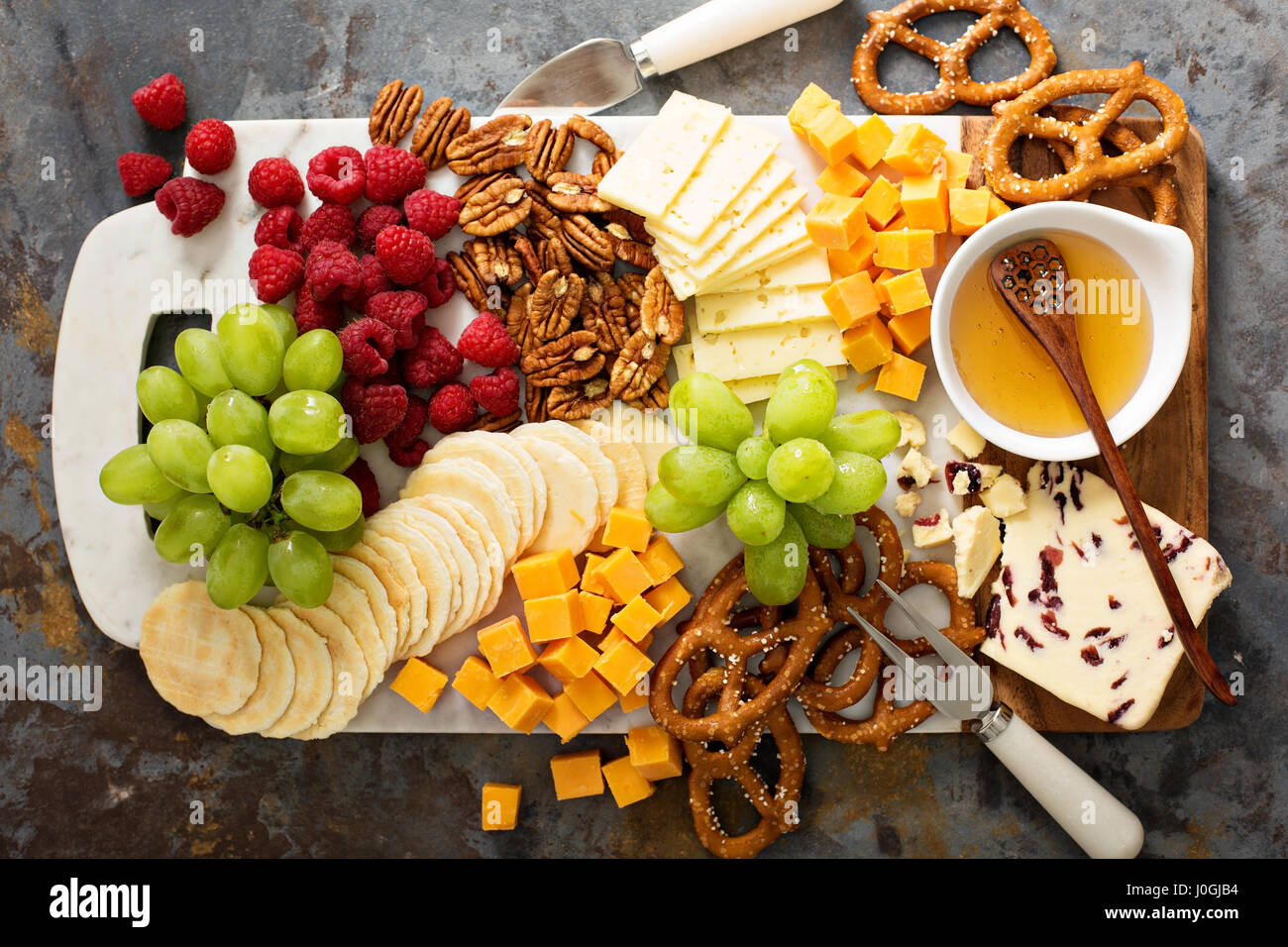 Cheese and snacks platter with honey and fresh fruit - Stock Image