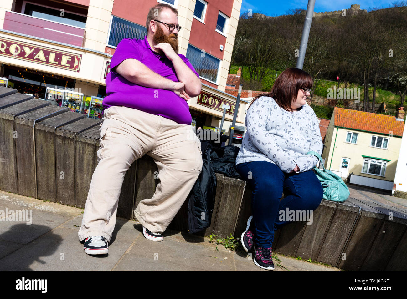 Obesity in UK fat people sat resting inbetween meals fat middle fat belly fat bellies overweight people unhealthy - Stock Image