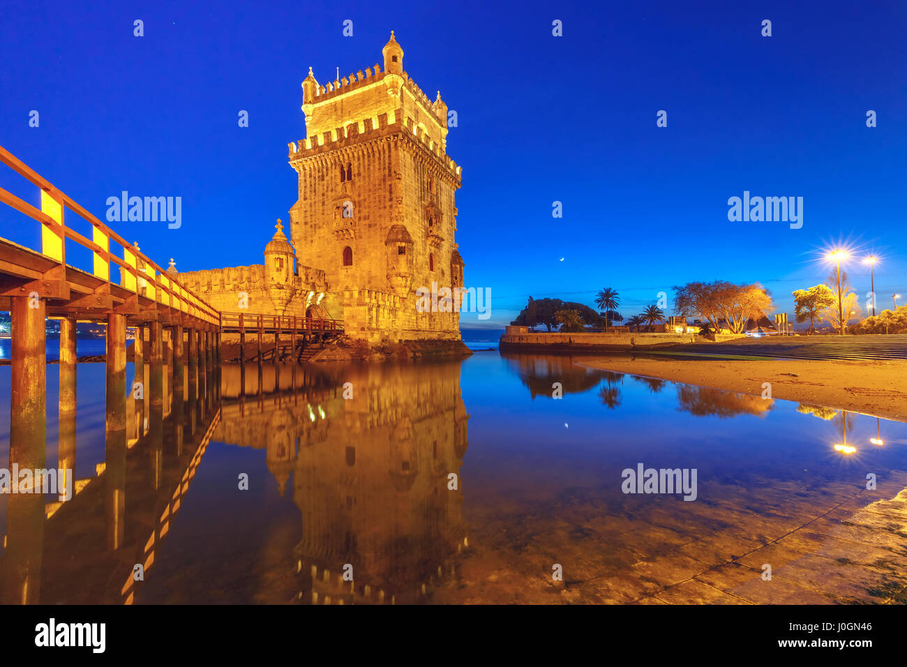 Belem Tower or Tower of St Vincent on the bank of the Tagus River during evening blue hour, Lisbon, Portugal - Stock Image