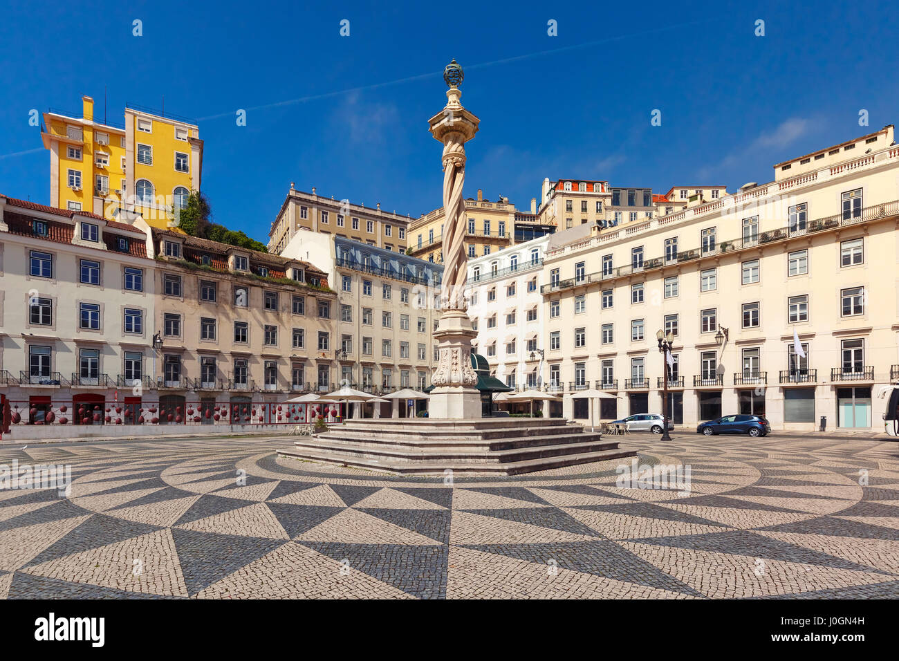 Town Hall Square with a beautiful geometric mosaic in Lisbon, Portugal. In the center of the square the pillory - Stock Image