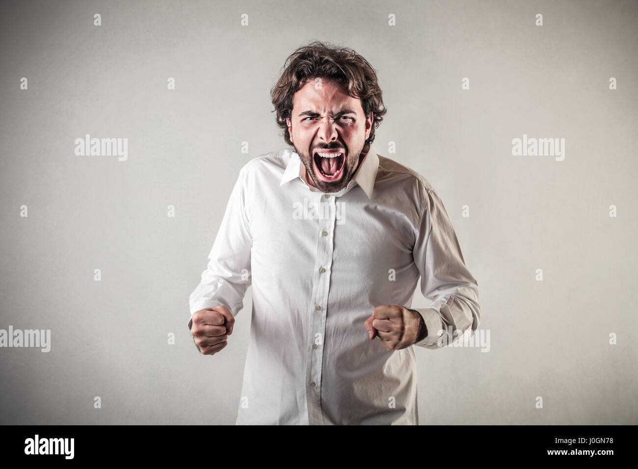 Businessman yelling in madness - Stock Image