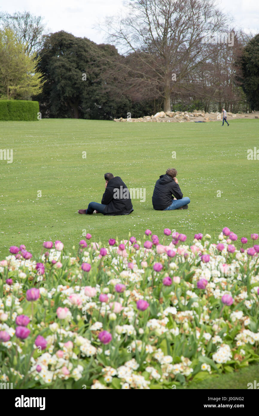 Two men with their backs to each other talking on mobile phones. - Stock Image